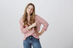 Follow me there. Studio shot of confident friendly teenage girl with blonde hair and positive smile in stylish striped. Sweater and jeans posing and pointing Stock Photos