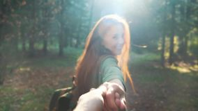 Follow me to the adventures. Young beautiful red-haired girl with a backpack. Follow the adventure in the forest. Holds. The hand of a guy or a man stock video footage