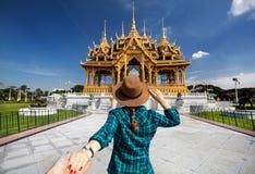Follow me to Bangkok. Woman in hat and green checked shirt leading man to the Ananta Samakhom Throne Hall in Thai Royal Dusit Palace, Bangkok, Thailand stock image