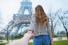 Follow me to Paris. Beautiful young girl near the Eiffel tower, follow me concept stock photography
