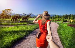 Follow me to Topiary Garden. Woman in orange dress and hat holding man by hand and going to Topiary Garden with elephants Royalty Free Stock Photos