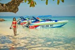 Follow me, Tourist girl walking on a paradisiac beach next speed boat Stock Images