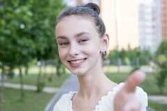 Follow me with woman. Follow me. Portrait of joyful girl stretching arms forward and smiling. Woman with perfect smile in a park and looking at camera against royalty free stock photos