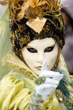 Follow my finger. A venetian women in a yellow costume with strong eye contact Stock Image
