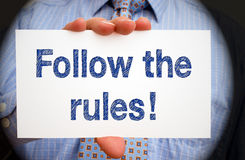 Follow the rules - Manager holding sign with text. Follow the rules - Manager holding white sign with text in his hand, spotlight effect Royalty Free Stock Image