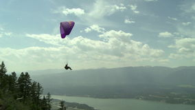 Follow shot of a paraglider launching into flight stock video footage