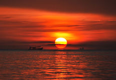 Follow the sun. Red sunset with big sun and boat Royalty Free Stock Image