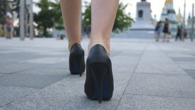 Follow to female legs in high heels shoes walking in urban street. Feet of young business woman in high-heeled footwear Royalty Free Stock Image