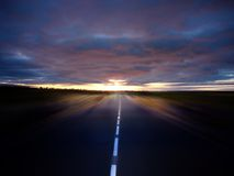 Follow to the sun. Straight road under stormy sky with motion blur as speed effect Royalty Free Stock Image