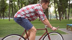 Follow to young handsome man riding a vintage bicycle outdoor. Sporty guy cycling at the park. Healthy active lifestyle royalty free stock photos