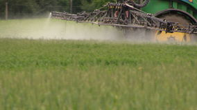 Follow tractor spray field plants with chemical pesticide stock video footage