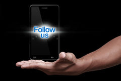 Follow us. Hand showing smartphone with follow us icon stock photos