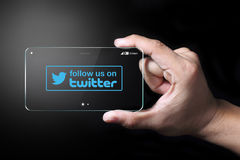 Follow us on Twitter icon. Johor, Malaysia - Transparent smartphone, follow us icon on Twitter with hand on dark background. Twitter is famous social networking stock illustration