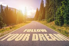 Follow your dream text written on road in the mountains.  stock images