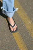 Follow Your Dreams. Foot stands on yellow line on highway.  Blue jean with rolled up cuff.  Foot in flipflops Stock Photography