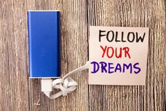 Follow your dreams motivational handwritten message on white paper above retro wooden background. Concept with positive motivation royalty free stock image