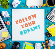 Follow your dreams. Office table desk with supplies, white blank note pad, cup, pen, pc, crumpled paper, flower on blue Royalty Free Stock Photo