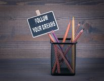 Follow your dreams. A small blackboard chalk and colored pencil on wood background royalty free stock photo