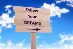 Follow your dreams sign. Follow your dreams wooden sign with blue sky background Stock Images