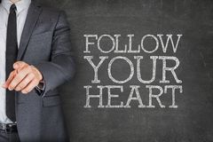 Follow your heart on blackboard with businessman Royalty Free Stock Photography