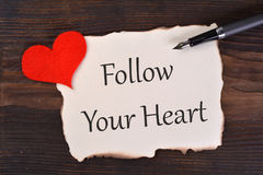 Follow Your Heart. Word in burned paper with heart and pen on wood stock photo