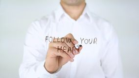 Follow Your Heart, Man Writing on Glass royalty free stock photos
