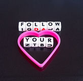 Follow your heart. Text ' follow ' and ' your ' inscribed on small white cubes in uppercase letters with a heart shape to complete the concept of follow your Stock Photo