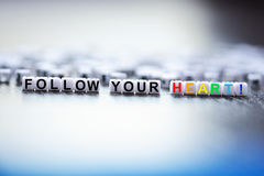 Follow your heart text spelled with plastic letter beads Royalty Free Stock Images