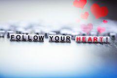 Follow your heart text spelled with plastic letter beads Royalty Free Stock Photo