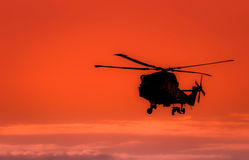 The follower. Helicopter and bird silhouette in the sunset sky,bird following the helicopter Stock Photos