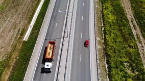 Following aerial view of a red retro car drive on road or highway in the middle of the day. Not a lot of cars on stock footage