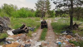 Following back view of environmental inspector or forester riding atv quadbike through forest polluted with plastic and