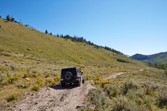 Following behind a 4WD vehicle vehicle. Driving along a dirt track through the mountains during an off road expedition Stock Image