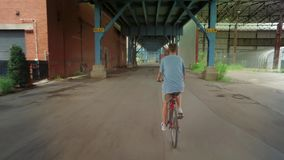 Following Biker Under Bridge in City Industrial Area. Following a biker riding under the 31st Street Bridge in Pittsburgh`s industrial district stock video