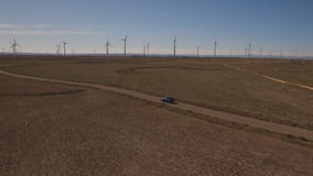 Following a black car in windmill farm stock footage