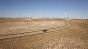 Following a black car in windmill farm, curved road stock video