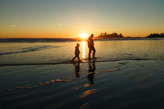 Following His Hero. Father and son walking in the surf at Chesterman Beach in Tofino, British Columbia Royalty Free Stock Photography