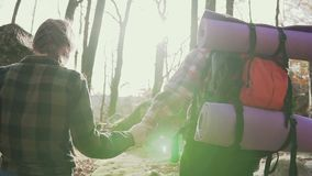 Following me - a happy young man with a backpack on his shoulders and a camera in his hands, pulling the girl with his. Hand - hand in hand went in the fall on stock footage