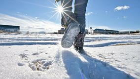Following the men`s feet in jeans and warm shoes walking in the snow on a winter sunny day. Close-up low angle. Back. View stock video footage