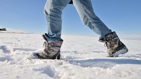 Following the men`s feet in jeans and warm shoes walking in the snow on a winter sunny day. Close-up low angle. Side. View stock video footage