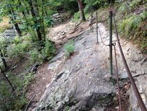 Following the path. Hand railing marks a hiking trail over rocks Stock Image