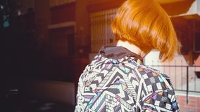 Following red haired attractive hipster young woman back slow Motion 4K . Fashionable footage stock footage