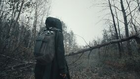 Following shot female wanderer in grunge mask hooded mantle walking in empty forest with bare trees. Apocalypse concept