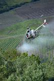 Following the spraying helicopter. Helicopter spraying pesticides. Chemical treatments by helicopter over the vineyards. Italy, Oltrepo pavese hills stock photography