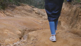 Following to female tourist in raincoat walking on stone mountain trail. Feet of woman hiking through a narrow canyon stock video footage