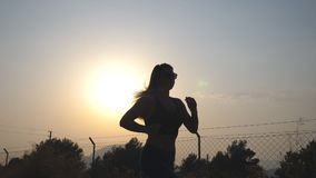 Following to sporty girl jogging in country road at sunrise. Young woman running outdoors at morning. Healthy active