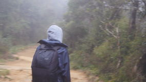 Following to tourist girl with backpack that walking along tropical forest. Hiking woman in raincoat going in wet wood stock video footage