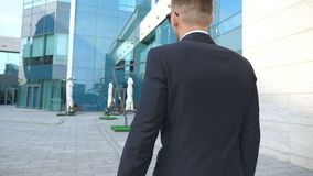 Following to young businessman with a briefcase walking near modern office building. Business man in sunglass commuting. To work. Confident guy in suit going in stock video