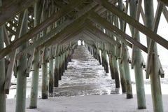 Folly Beach South Carolina, February 17, 2018 - view down beach and ocean under fishing pier.  stock photography