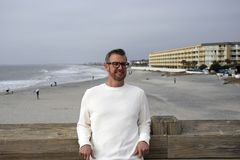 Folly Beach South Carolina, February 17, 2018 - white male model wearing long white shirt leaning against pier railing with beach royalty free stock images